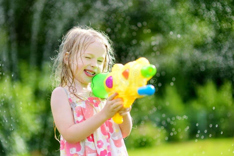 Het aanbiddelijke meisje spelen met waterkanon op hete de zomerdag Leuk kind die pret met water hebben in openlucht royalty-vrije stock foto's