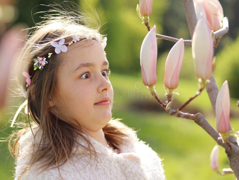 Het aanbiddelijke meisje is verrast en het verbaasde bekijken magnoliaknoppen in de bloeiende de lentetuin royalty-vrije stock foto