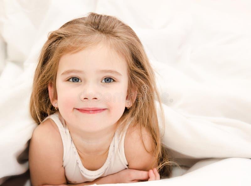 Het aanbiddelijke meisje waked omhoog in haar bed royalty-vrije stock foto