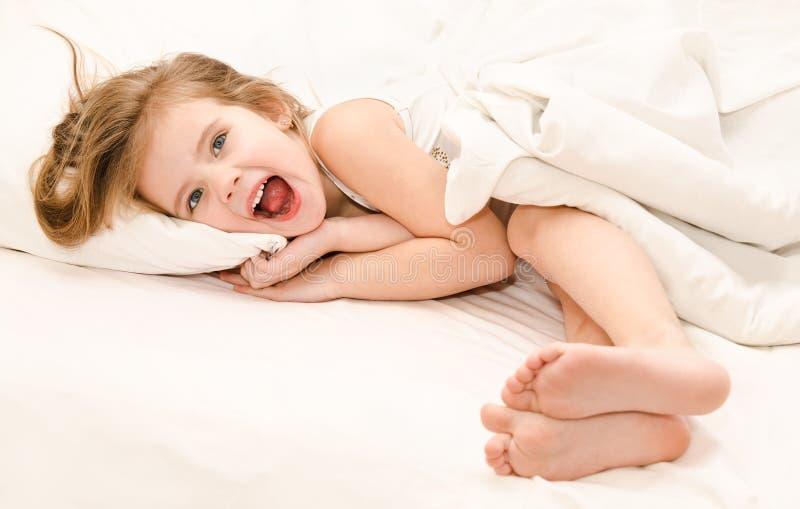 Het aanbiddelijke meisje waked omhoog in haar bed royalty-vrije stock foto's