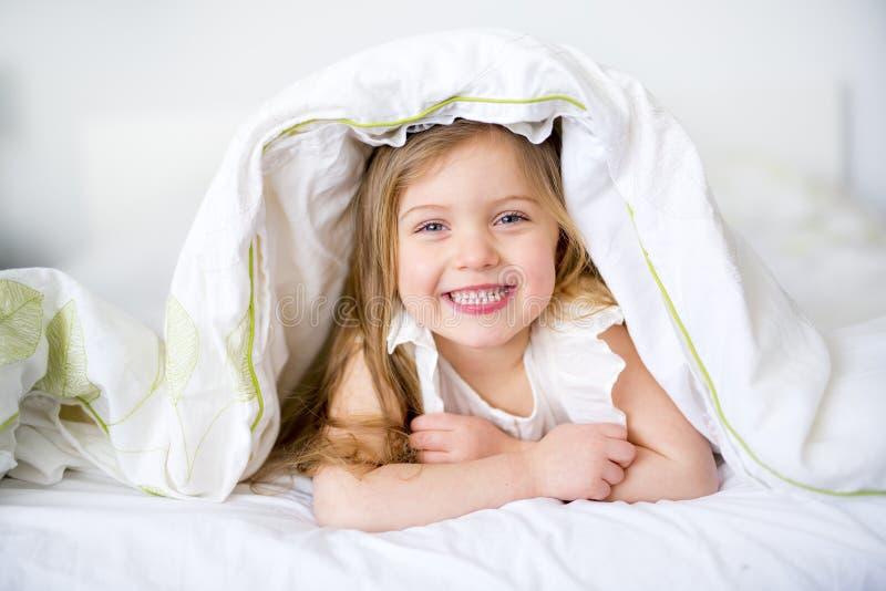 Het aanbiddelijke meisje waked omhoog in haar bed stock afbeeldingen