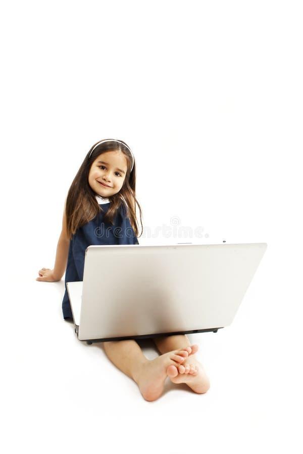 Het aanbiddelijke meisje zit op vloer met haar laptop stock afbeeldingen