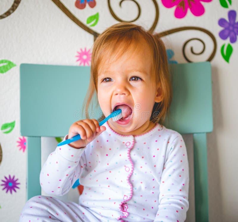 Het aanbiddelijke Peutermeisje borstelt Haar Tanden in Pyjama's Het concept van de gezondheidszorg royalty-vrije stock foto