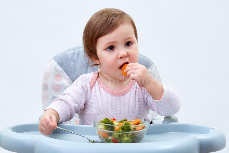 Het aanbiddelijke peutermeisje heeft pret terwijl het eten van gestoofde groenten op witte achtergrond stock foto's
