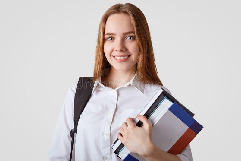Het aanbiddelijke schoolmeisje met blauwe ogen, het glanzen glimlach, draagt elegant wit overhemd, draagt boeken en de rugzak, he stock foto