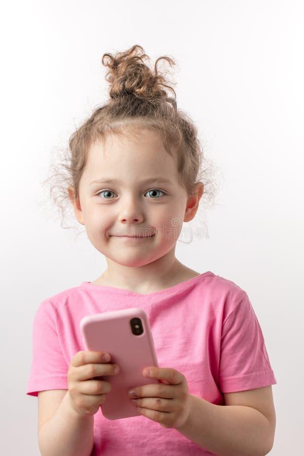 Het aanbiddelijke vrolijke meisje speelt online spelen op de celtelefoon stock afbeelding