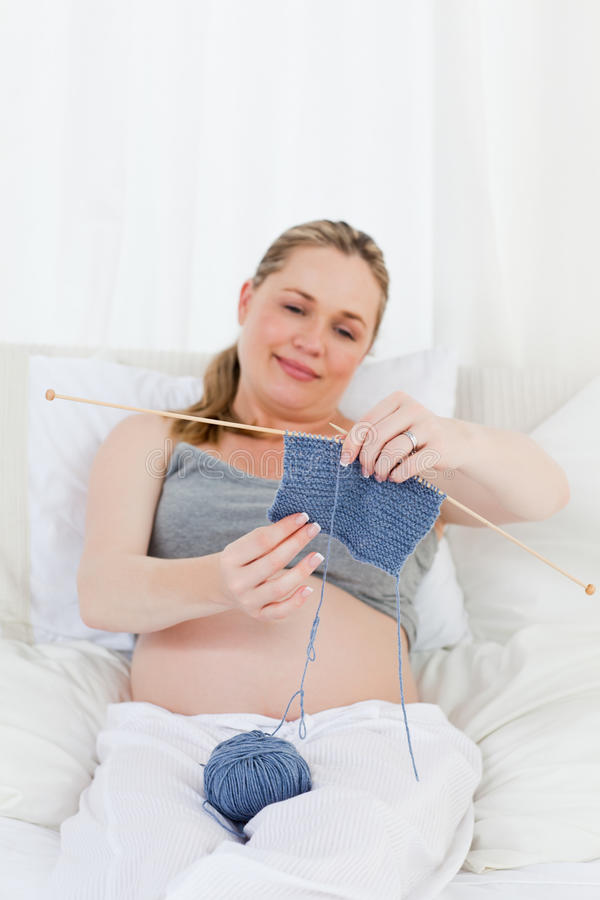 Het aanbiddelijke zwangere vrouw breien op haar bed stock fotografie