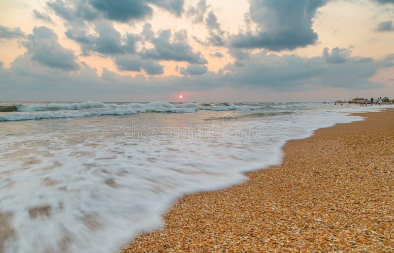 Het aankomen golf op het strand bij zonsondergang op winderige dag royalty-vrije stock fotografie