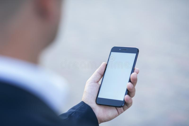 Het aanrakingsscherm van een mobiele telefoon, in de hand van een zakenman Foto voor Spot omhoog stock fotografie