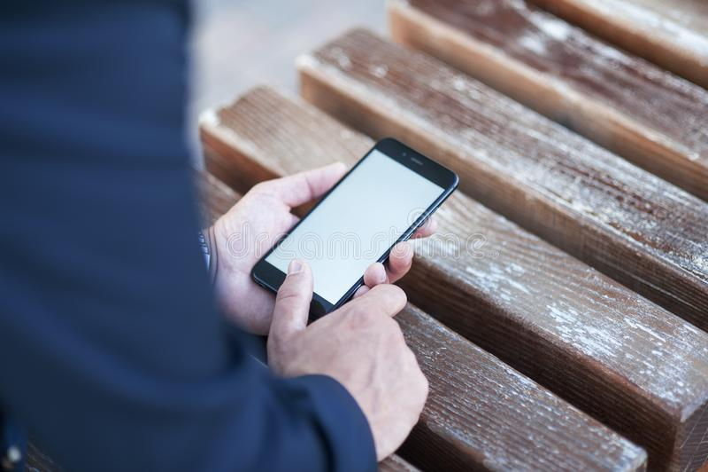 Het aanrakingsscherm van een mobiele telefoon, in de hand van een zakenman Foto voor Spot omhoog stock afbeelding