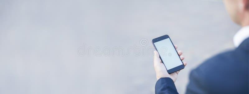 Het aanrakingsscherm van een mobiele telefoon, in de hand van een zakenman Een lange foto voor Spot omhoog royalty-vrije stock foto
