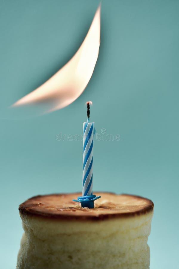 Het aansteken van een verjaardagskaars op een kaastaart stock foto