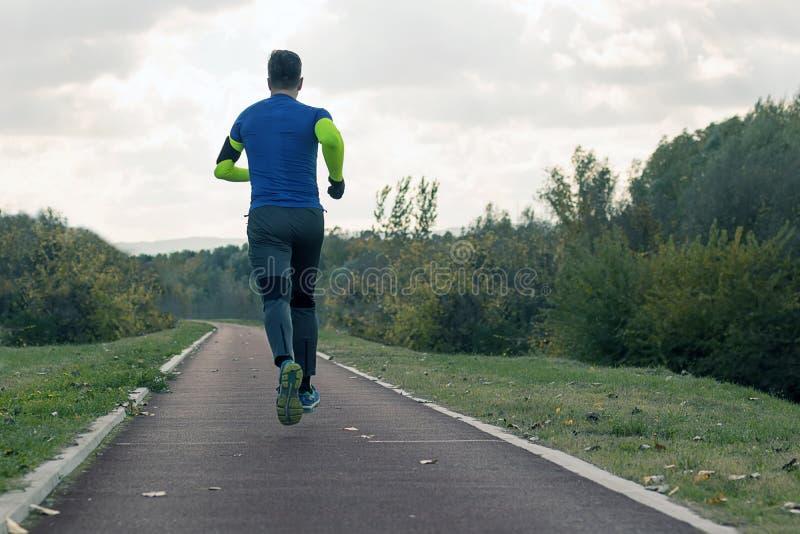 Het aanstoten in het park Jonge mens in sporten die jogging in pari kleden stock fotografie