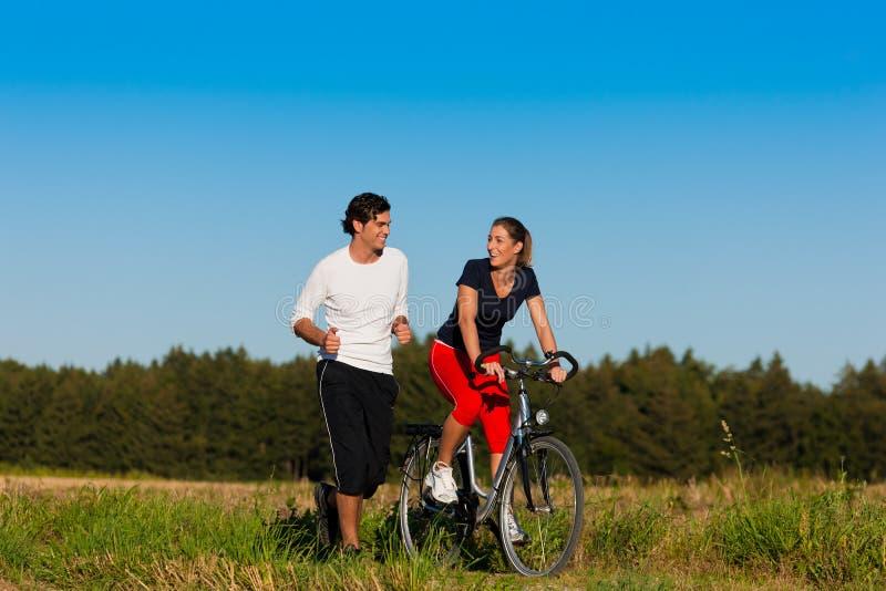 Het aanstoten van de man en van de vrouw en met fiets