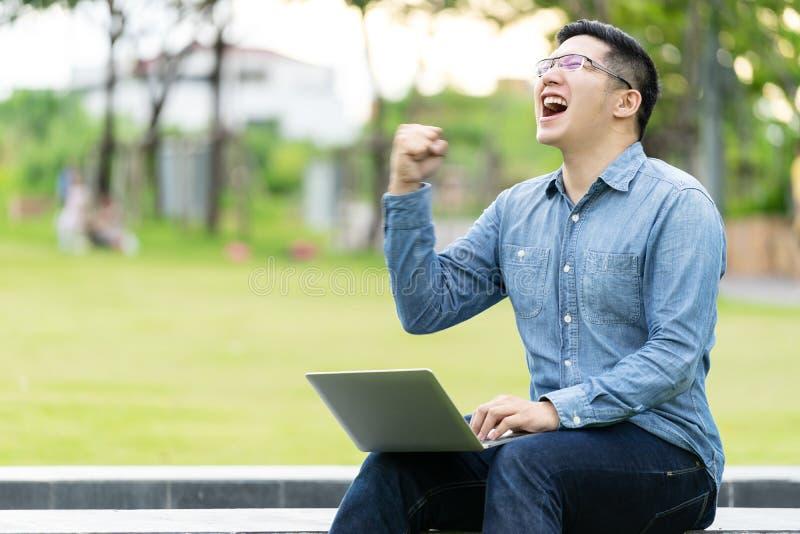 Het aantrekkelijke Aziatische gelukkige mensengebaar of heft opgewekte hand op het gillen van ja het lezen van online goed nieuws stock foto's