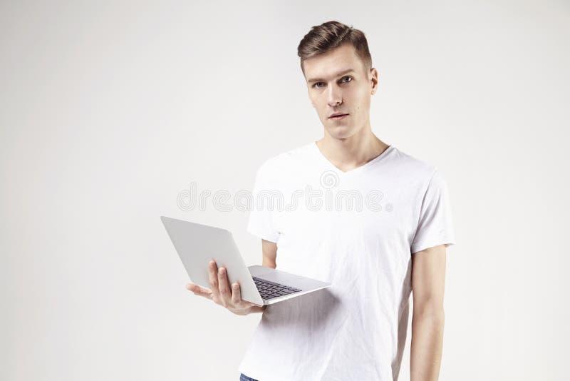 Het aantrekkelijke bedrijfsmensenmodel in witte t-shirt isoleerde op witte greeplaptop in rechts Verrast gezicht royalty-vrije stock foto