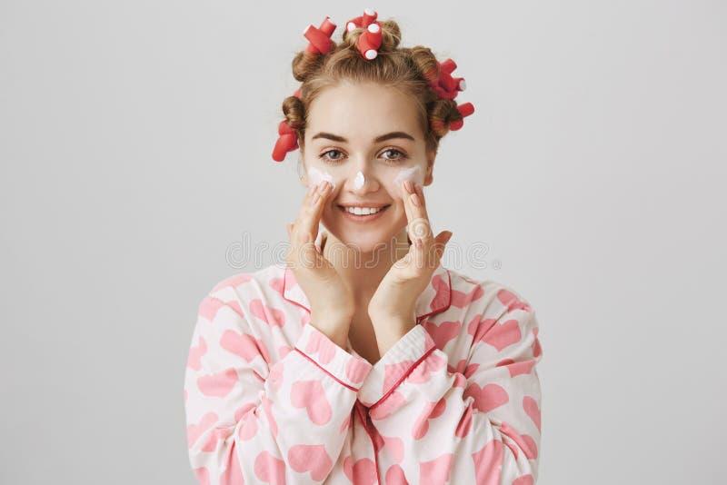Het aantrekkelijke blonde Kaukasische model in haar-krulspelden, het van toepassing zijn roomt of maskeert op wangen en neus af,  stock fotografie
