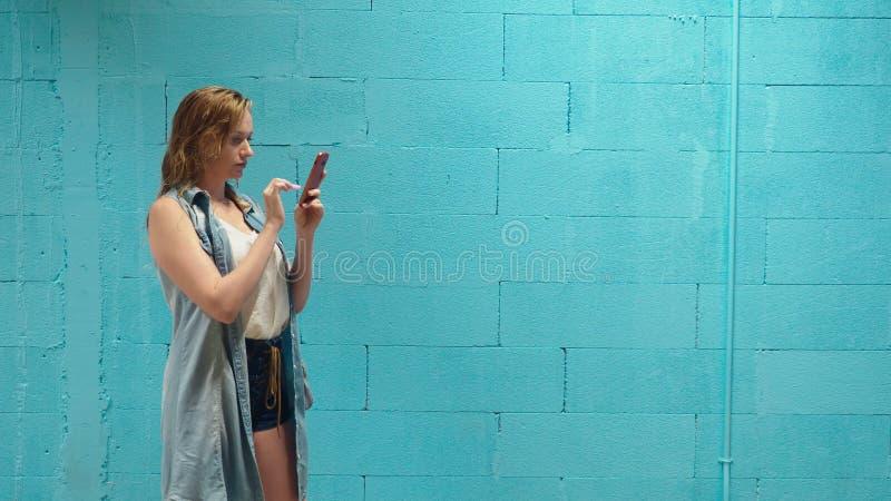 Het aantrekkelijke blondemeisje gebruikt rode smartphone tegen een blauwe muur royalty-vrije stock foto's