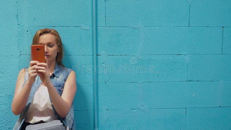 Het aantrekkelijke blondemeisje gebruikt rode smartphone tegen een blauwe muur royalty-vrije stock fotografie