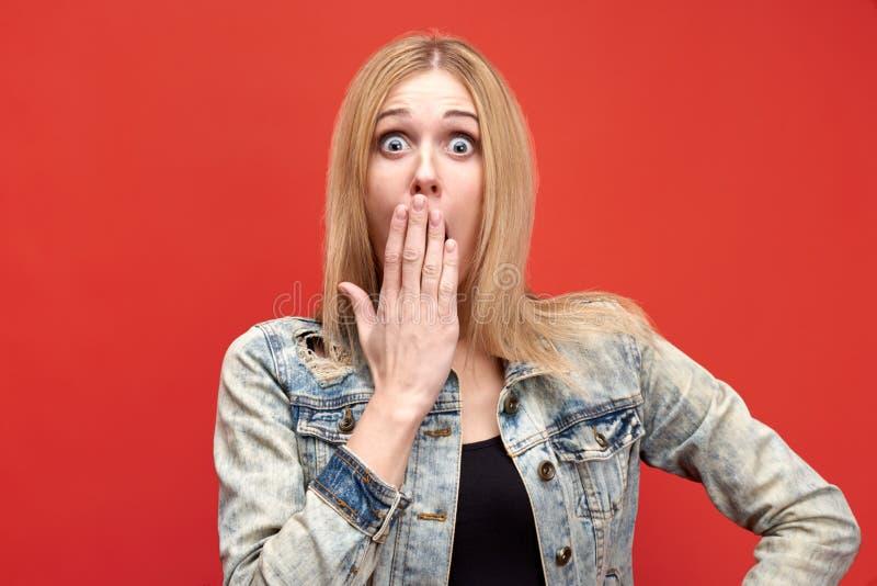 Het aantrekkelijke blondemeisje met lang haar in schok opent wijd open ogen en behandelt haar open mond met haar hand royalty-vrije stock afbeeldingen
