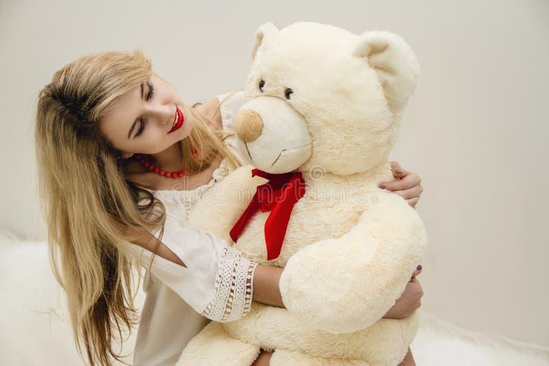 Het aantrekkelijke blondemeisje met mooie ogen zit op haar bed en het koesteren van een Teddybeer Vrouw in lichte witte kleding S stock afbeeldingen