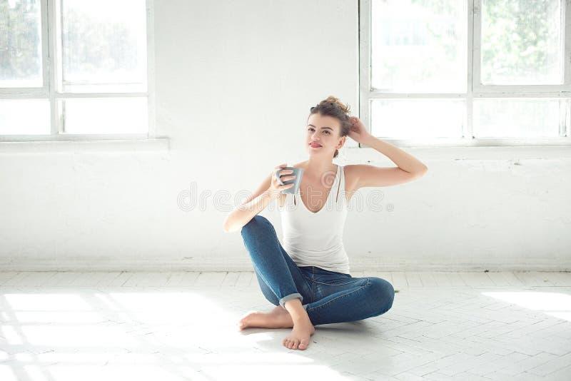 Het aantrekkelijke blootvoetse vrouw ontspannen op de vloer stock foto's