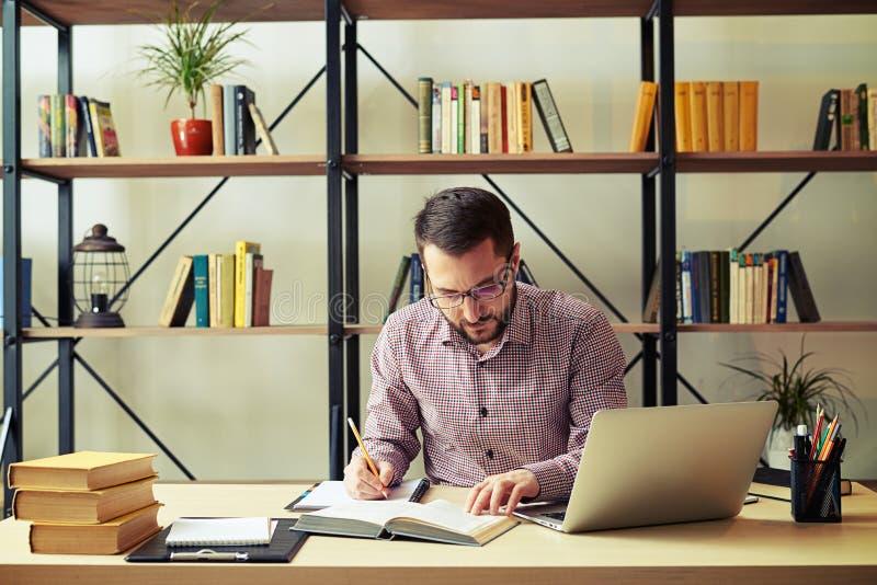 Het aantrekkelijke boek van de zakenmanlezing en thuis weg het nemen van nota's stock afbeelding