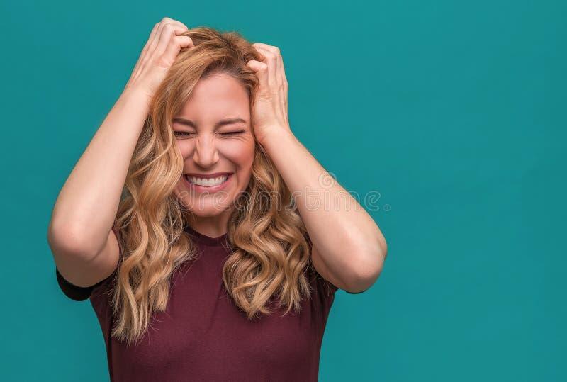 Het aantrekkelijke boze blondemeisje houdt boos haar hoofd Boze jonge vrouw op blauwe achtergrond stock fotografie