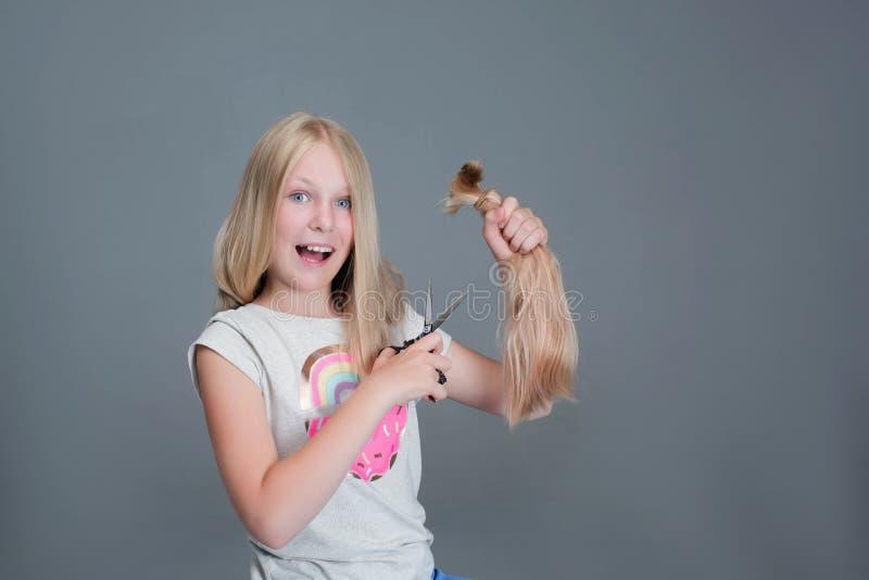 Het aantrekkelijke chaildmeisje snijdt haar lang blond natuurlijk haar stock afbeelding