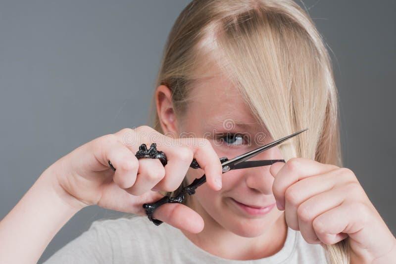 Het aantrekkelijke chaildmeisje snijdt haar lang blond natuurlijk haar royalty-vrije stock foto