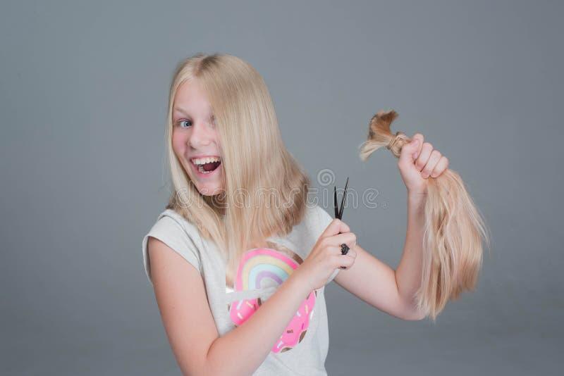 Het aantrekkelijke chaildmeisje snijdt haar lang blond natuurlijk haar stock foto