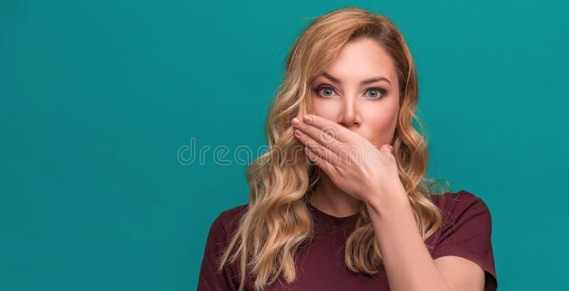 Het aantrekkelijke die blonde houdt hand bij mond, op een blauwe achtergrond wordt verrast of wordt gesloten royalty-vrije stock fotografie