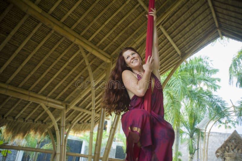 Het aantrekkelijke en atletische aerialistvrouw hangen van zijdestof die lucht het dansen training opleiding gelukkig bij mooie h stock afbeeldingen