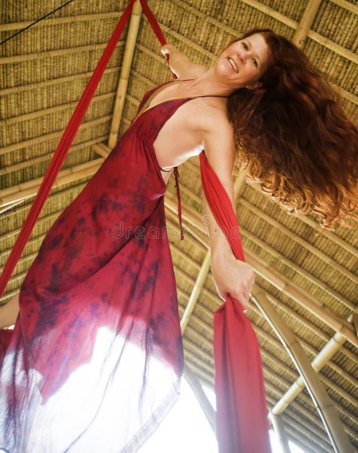 Het aantrekkelijke en atletische aerialistvrouw hangen van zijdestof die lucht het dansen training opleiding gelukkig bij mooie h royalty-vrije stock afbeelding