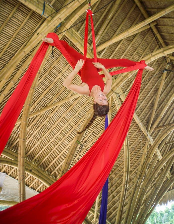 Het aantrekkelijke en atletische aerialistvrouw hangen van zijdestof die lucht het dansen training opleiding gelukkig bij mooie h stock foto