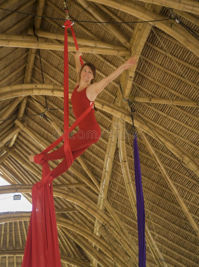 Het aantrekkelijke en atletische aerialistvrouw hangen van zijdestof die lucht het dansen training opleiding gelukkig bij mooie h stock foto's