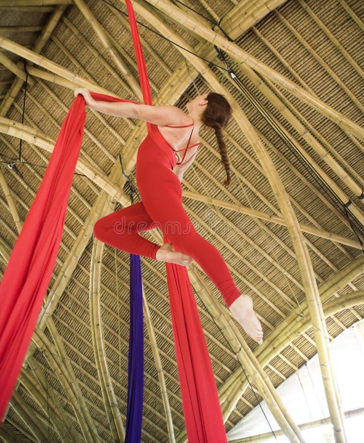 Het aantrekkelijke en atletische aerialistvrouw hangen van zijdestof die lucht het dansen training opleiding gelukkig bij mooie h royalty-vrije stock foto