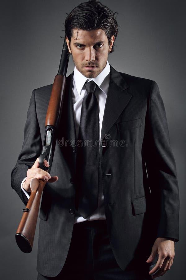 Het aantrekkelijke en elegante mens stellen met jachtgeweer stock afbeeldingen