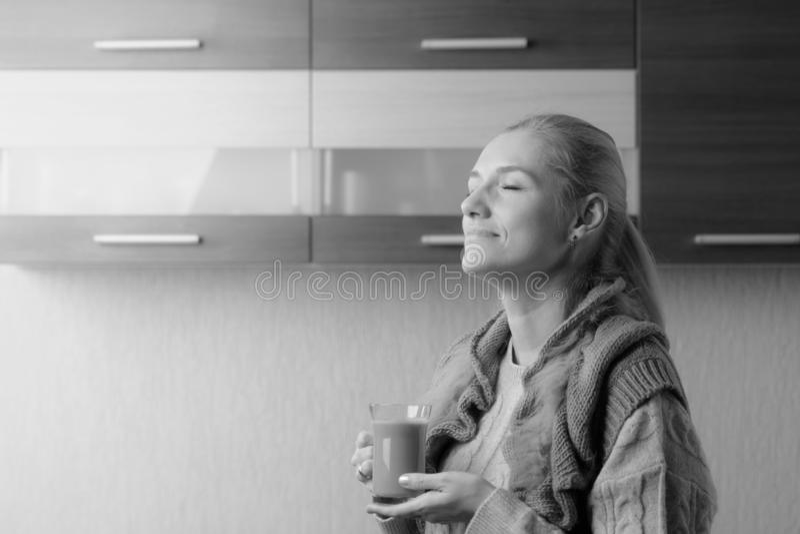 Het aantrekkelijke en gelukkige blonde in sweater drinkt latte royalty-vrije stock fotografie