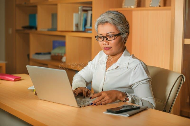 Het aantrekkelijke en gelukkige succesvolle rijpe Aziatische vrouw werken ontspande bij laptop computerbureau glimlachen zeker in stock afbeelding