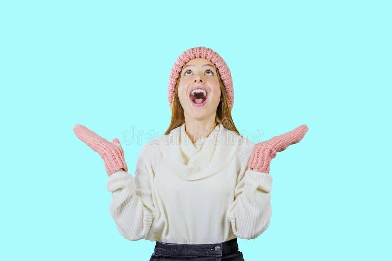 Het aantrekkelijke en jonge meisje in een hoed en vuisthandschoenen met verbazing kijkt upwards en richt handen op een geïsoleerd stock foto