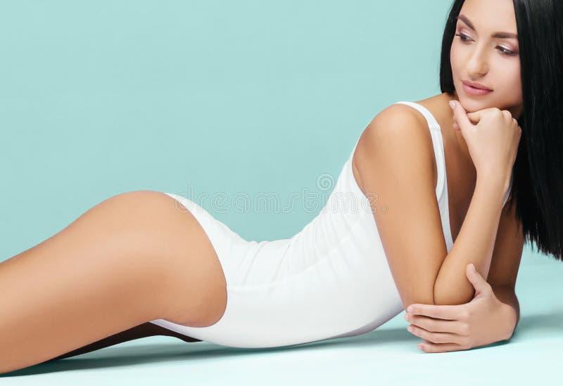 Het aantrekkelijke en sportieve vrouw stellen in wit zwempak Geschikt en atletisch lichaam Mooi meisje in zwempak Geschiktheid, d stock afbeeldingen