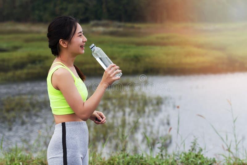 Het aantrekkelijke gezonde drinkwater van het geschiktheidsmeisje na training Het agentmeisje neemt een rust na opleiding stock afbeelding