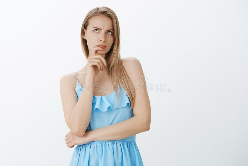 Het aantrekkelijke glamour Europese wijfje met eerlijk haar in het blauwe kleding proberen denkt hard het fronsen wat betreft lip stock afbeeldingen