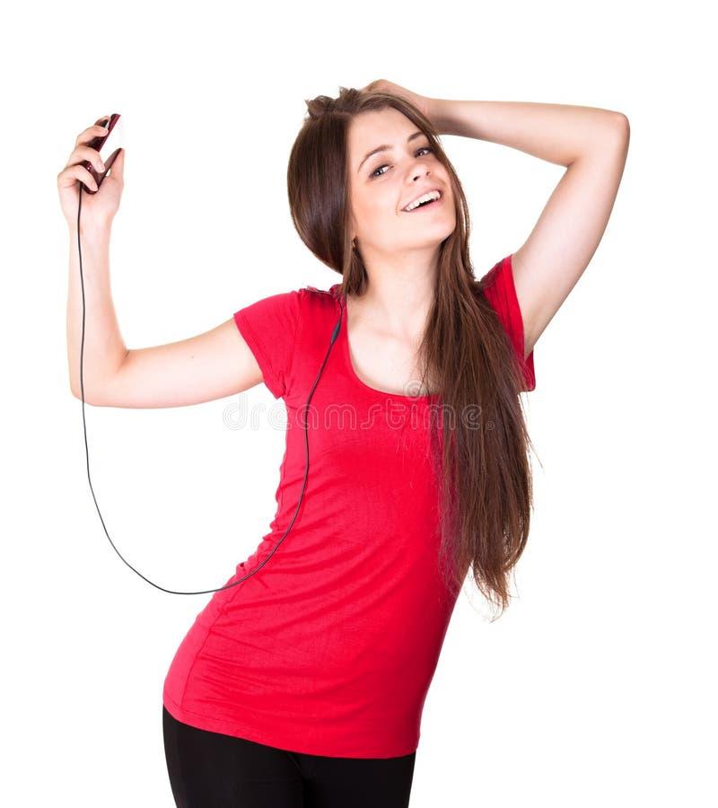 Het aantrekkelijke glimlachende tienermeisje luistert muziek stock afbeelding