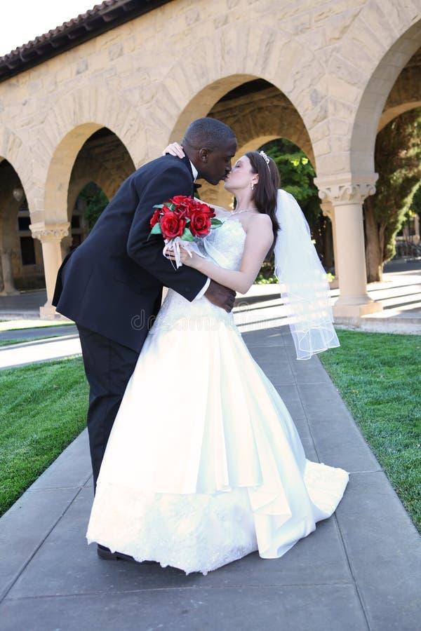 Het aantrekkelijke Interracial Kussen van het Paar van het Huwelijk stock fotografie