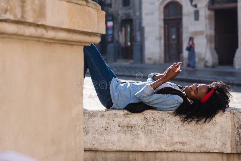 Het aantrekkelijke jonge Afrikaanse meisje ligt op de fontein en babbelt gelukkig op de mobiele telefoon royalty-vrije stock foto
