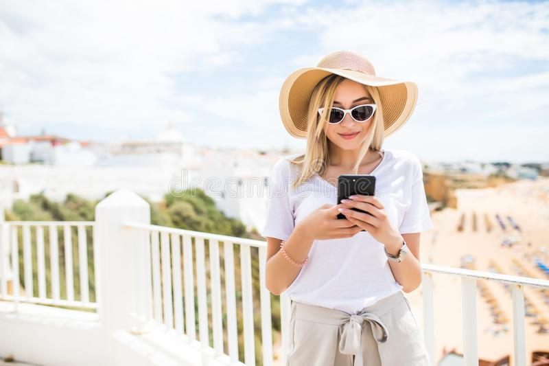 Het aantrekkelijke jonge blondevrouw typen op telefoon op terras op de achtergrond van de strandmening royalty-vrije stock afbeelding