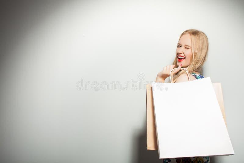 Het aantrekkelijke jonge meisje is gek over het winkelen royalty-vrije stock afbeelding