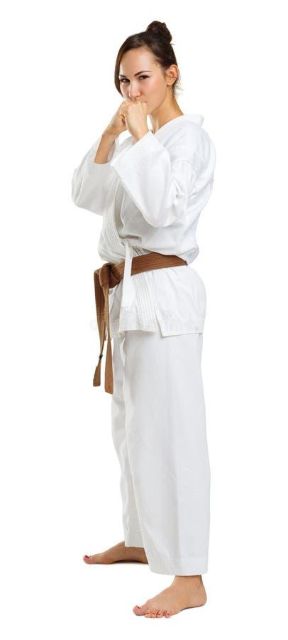 Het aantrekkelijke jonge meisje in karate stelt Geïsoleerdj op witte achtergrond stock foto's